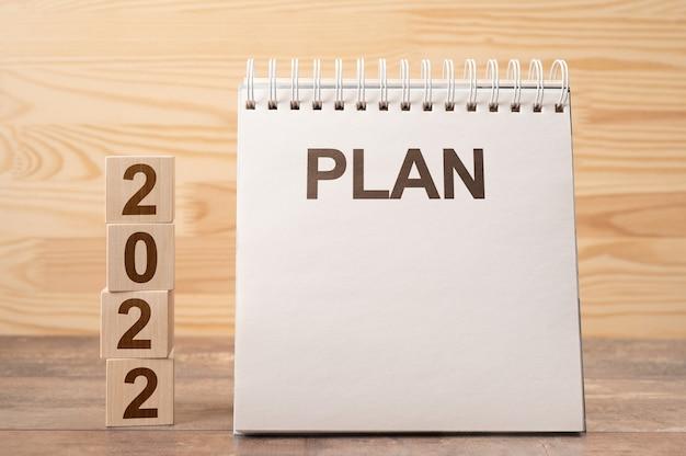새로운 시작을위한 2022 년. 계획 단어와 2022 큐브 나무 테이블 배경.