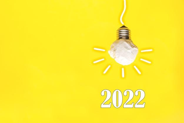2022年黄色の背景に白い紙の電球、革新的なビジネスビジョンと解像度、バイオ燃料クリーンエネルギーの概念