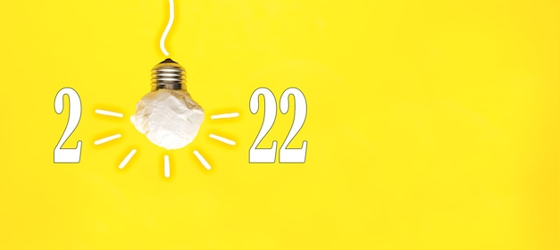 2022  white paper light bulb on yellow background, innovative business vision and resolution