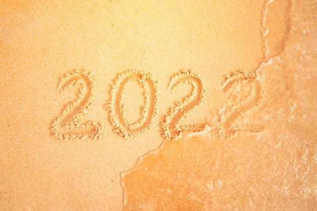 熱帯のビーチで、砂で書かれた2022年。年の変更の概念。海の波が碑文を洗い流します。暖かい国での年末年始のお祝い。