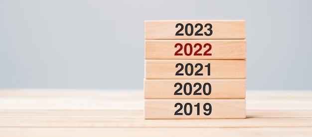 Блок 2023 года над деревянным зданием 2022, 2021 и 2020 годов на фоне стола. бизнес-планирование, управление рисками, разрешение, стратегия, решение, цель, новый год и концепции счастливого праздника