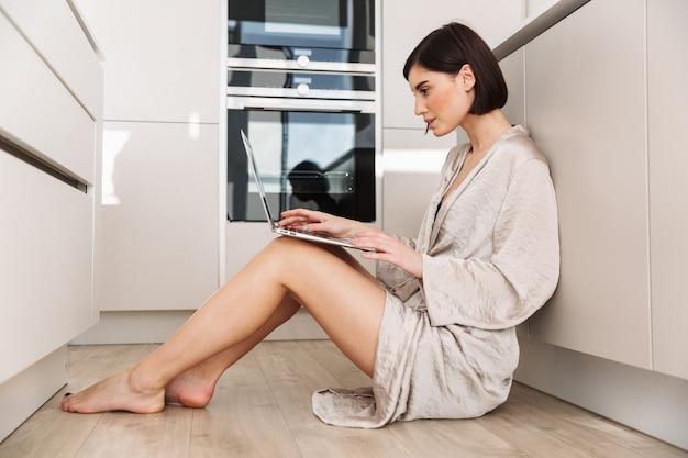 Фотография в профиль худой женщины 20 лет, одетой в халат, сидящей на полу на кухне и работающей, или общающейся онлайн на персональном компьютере