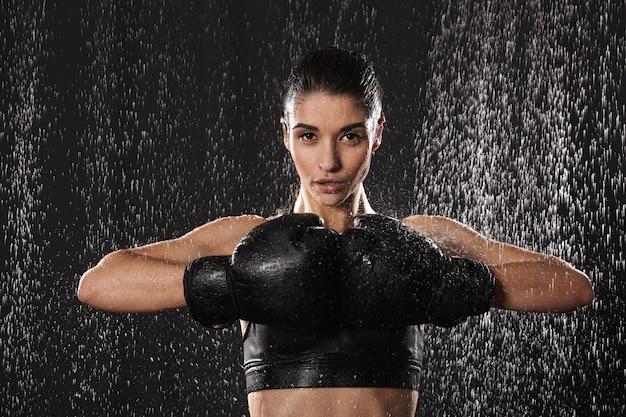 Сильный фитнес женщина-боец 20-х годов в спортивной одежде, держа черные боксерские перчатки вместе во время тренировки под каплями дождя, изолированных на темном фоне