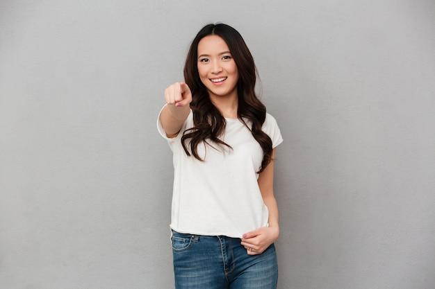 Фото содержимого женщины 20-х годов в повседневной футболке и джинсах, указывая пальцем на камеру с улыбкой, изолированных на серую стену