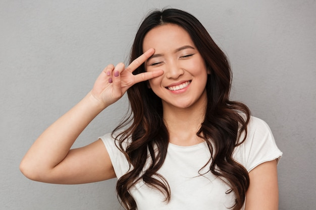 Портрет забавной китаянки 20-х в повседневной футболке с удовольствием и двумя пальцами на лице, изолированном над серой стеной