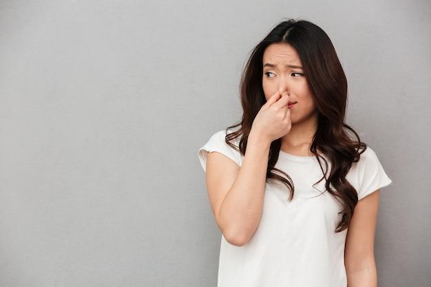 Портрет разочарованной женщины 20-х годов, сжимающей нос с отвращением на лице из-за неприятного запаха, изолированной над серой стеной
