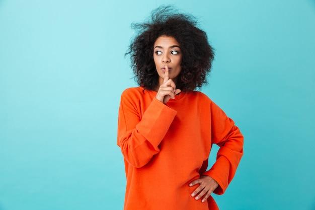 カジュアルな服装の唇に人差し指を押しながら水色の壁の上に孤立した沈黙を保つことを求めて20代のアフリカの女性の画像