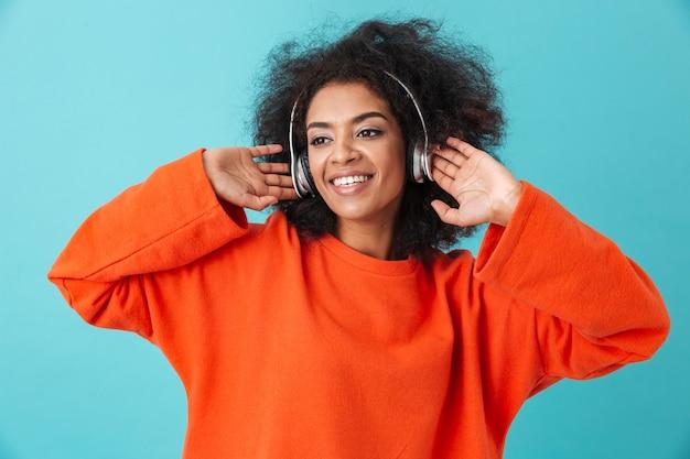 Довольная американка 20 лет с мохнатой прической наслаждается музыкой через беспроводные наушники, слушая любимую мелодию, изолированную над голубой стеной