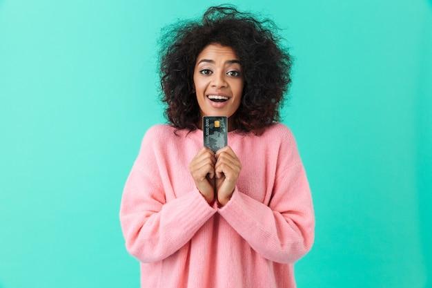 Портрет радостной американской женщины 20-х годов с афро прической, демонстрирующей пластиковую кредитную карту в руках, изолированную над синей стеной