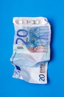 青い背景の上に20ユーロ紙幣がしわになっていました。