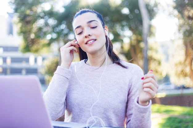 緑豊かな公園でリラックスし、イヤホンで携帯電話を使用してカジュアルな服装で若い女性20代