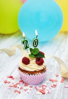 数字20キャンドルとカップケーキ