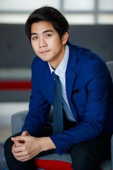20代の先見の明のある若いハンサムなアジアのエグゼクティブビジネスマンは、フォーマルなスーツを着て、リラックスして快適に足を組んで座って、成功への決意と自信を持ってカメラを見ています。