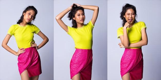 ファッションモデルとしての20代の若いアジア人女性は、緑色のシャツとネオンピンクのショートスカート、シリコンピンクのハンドバッグの財布のクラッチ、スタジオ照明の灰色の背景を分離、コラージュグループパックの肖像画を着用します