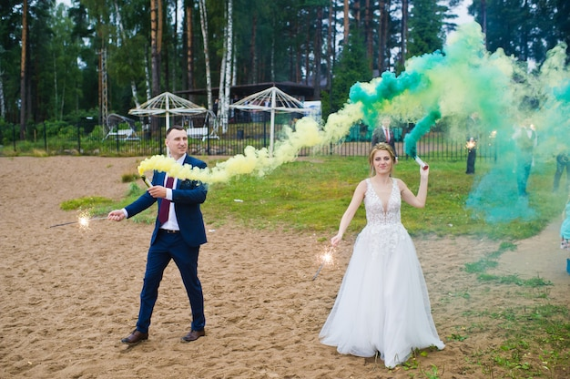 21.10.2019 russia, saint-petersburg, bride and groom with the blue and yellow colored smoke bombs