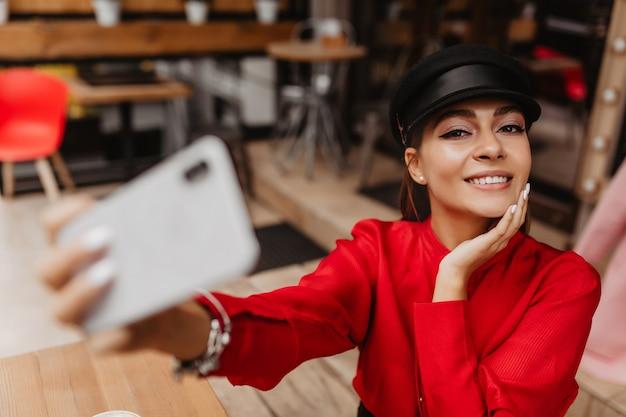 Modello femminile di 22 anni con un trucco nudo, vestito con un vestito rosso delicato, che completa il braccialetto d'argento, fa un selfie fantastico