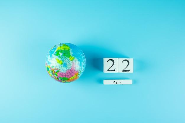 Глобус и 22 апреля календарь. счастливый день земли и концепция окружающей среды