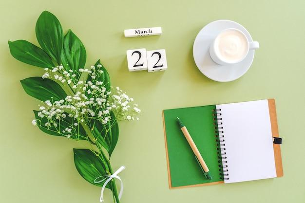 Деревянный кубик календарь 22 марта. блокнот, чашка кофе, букет цветов на зеленом фоне.