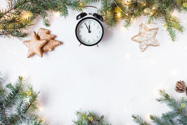 新年とクリスマスのコンセプト。クリスマスツリー、クリスマス目覚まし時計23:55、クッキー、光の花綱
