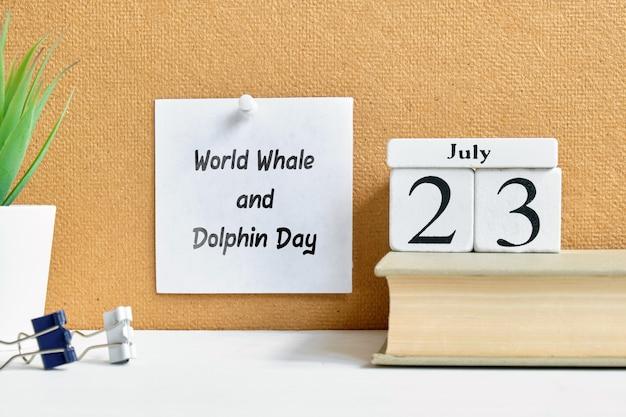 День кита и дельфина мира 23-ье июля - концепция календаря месяца двадцать третьего дня на деревянных блоках.