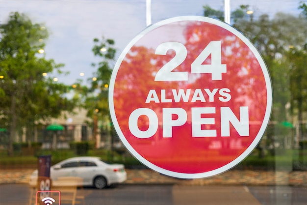 24 hours always open sign in front of the coffee shop cafe or co-working space in the town. 24 hours always open sign of department store shop near roadside. business shop concept