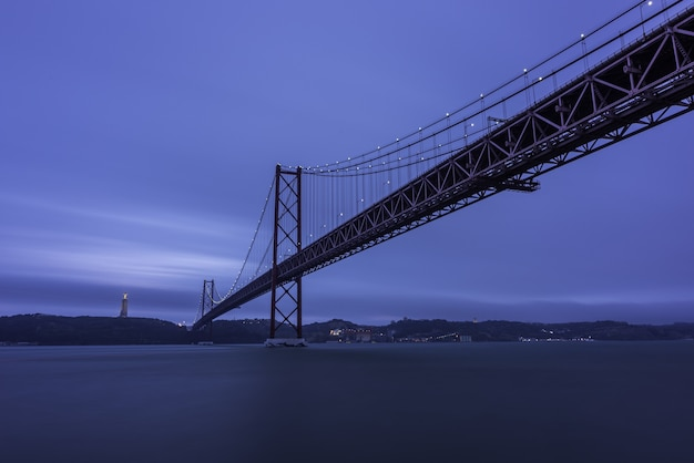 25 de abril bridge over the tagus river surrounded by hills and lights in the evening