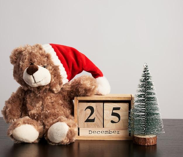 Коричневый мишка в красной шапке, настольный деревянный календарь с датой 25 декабря и зеленое декоративное дерево