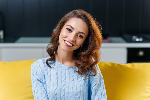 メガネをかけて、スタイリッシュな料理の背景にかわいい完璧な笑顔でカメラを見て、柔らかい青いセーターの美しい25歳の女の子。