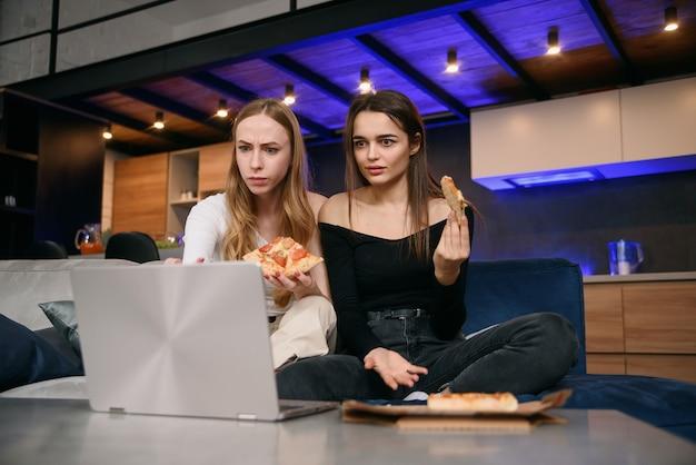 コンピューターで楽しい写真を閲覧中に快適なソファーに座っておいしいピザを楽しんでいる、驚きの魅力的な25代のスタイリッシュな女性の友人のスローモーション