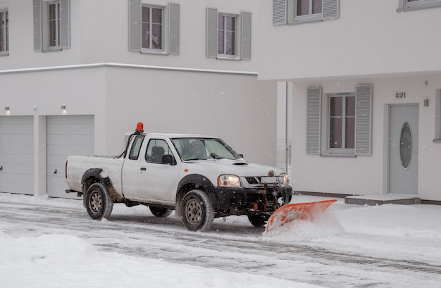 26.01.2021. piaseczno. poland. a pickup truck equipped with a plow is removing snow from a sloped driveway in winter.