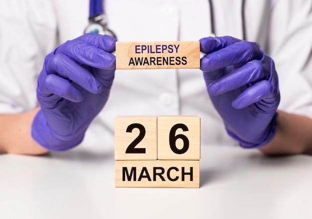 26 march, date on wooden calendar. world epilepsy purple day.