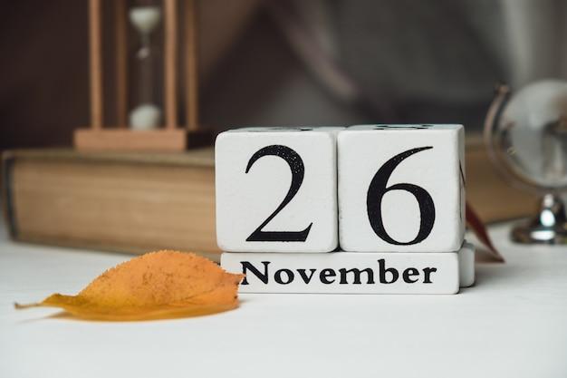 秋の葉の本の白い立方体から作られたカレンダーの11月26日