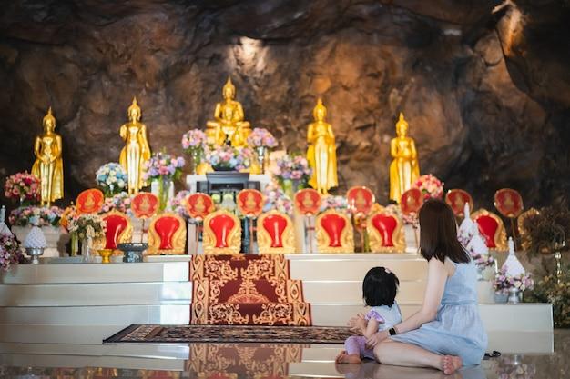 2021年3月27日、女性と娘がワットセンケオ寺院、アンファーチェンコンチンライで祈っています。タイ