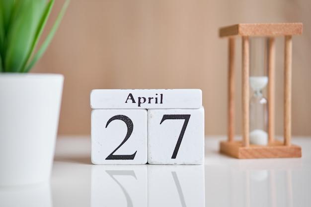 Дата на белых деревянных кубиках - двадцать седьмое, 27 апреля на белом столе. вид сверху.