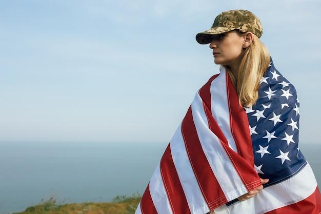 Гражданская женщина в военной фуражке мужа. вдова с флагом сша осталась без мужа. день памяти погибших воинов на войне. 27 мая - день памяти.