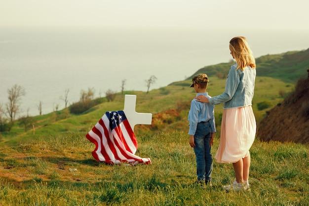 お母さんと息子は記念日27日に父親の墓を訪れました