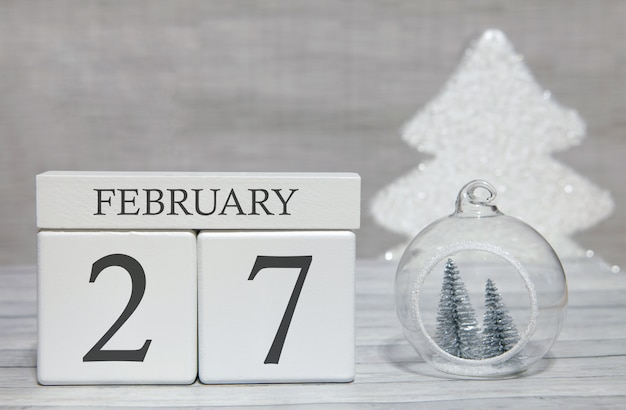 Календарь в форме куба на 27 февраля на деревянной поверхности и светлом фоне