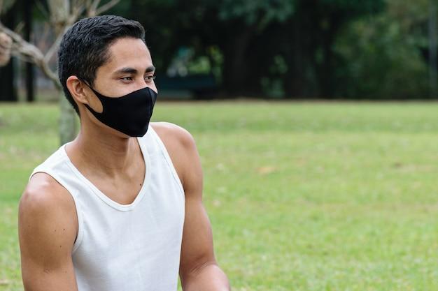 28세 브라질 청년, 마스크를 쓰고 녹색 잔디밭에 앉아 있습니다.