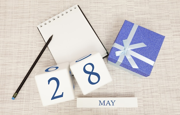 Календарь с модным синим текстом и цифрами на 28 мая и подарком в коробке.