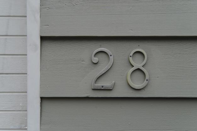 家の番号28サインオングリーン塗られた壁