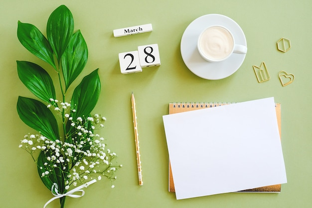 Деревянные кубики календарь 28 марта. блокнот, чашка кофе, букет цветов на зеленом фоне. концепция привет весна