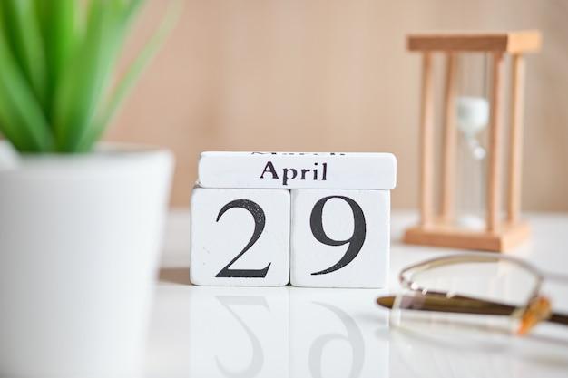 Дата на белых деревянных кубиках - двадцать девятого, 29 апреля 01 года на белом столе.