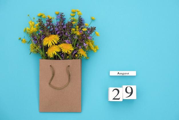 Деревянный кубик календарь 29 августа и красочные цветы в пакете ремесло на синем фоне.