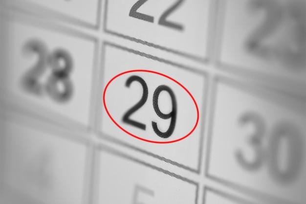 Планировщик календарного крайнего срока дня недели на белой бумаге 29
