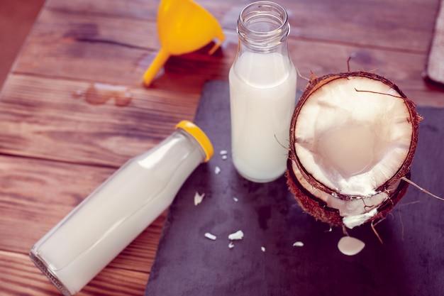 ココナッツ、ココミルクと漏斗が入った2本のボトル