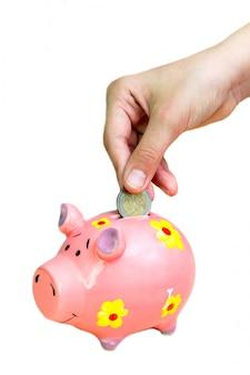 女の子はピンクの貯金箱にコイン2ユーロを入れます。