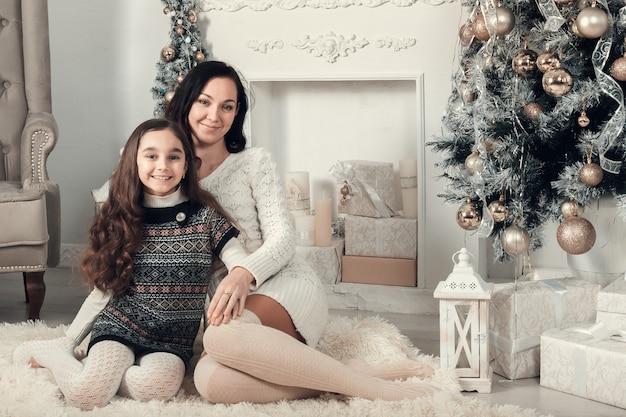 2人のかわいい女の子、母と娘がクリスマスの装飾が施された部屋の床に座っています。