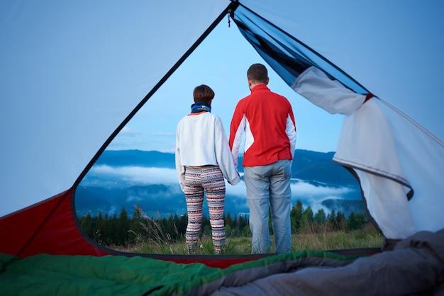 手を繋いでいる2人の若者の背面図は、霧が降りかかった山の朝の景色を楽しみます。テントの中からの眺め