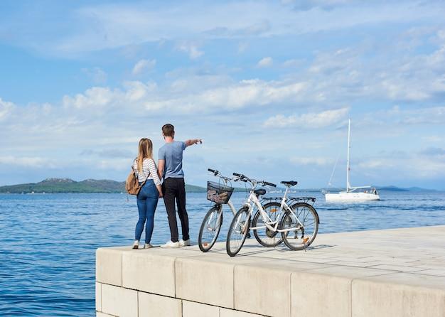 高い舗装された石の歩道に2つの自転車で立っている観光客カップル、男性と女性の背面図。