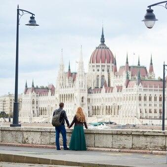 ハンガリー、ブダペストの国会議事堂。手を繋いでいる2つの古代のランタンの間にブダペストの壮大な建築の景色を楽しんでいる観光客のカップルの背面図